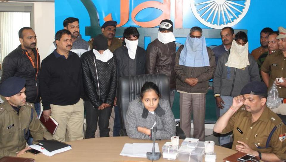 SSP Nivedita Kukreti Kumar (seated) presents the gang members (faces covered) before the media in Dehradun on Monday.