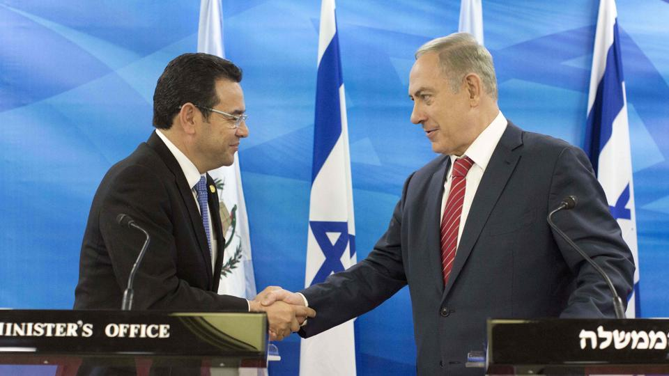 This file picture taken on November 28, 2016 shows Guatemalan President Jimmy Morales (L) and Israeli Prime Minister Benjamin Netanyahu (R) shaking hands during a joint press conference after signing bilateral agreements at the Prime Minister's Office in Jerusalem. Guatemala's President Morales announced he gave instructions to his foreign minister that the country's embassy in Israel should be moved to Jerusalem.