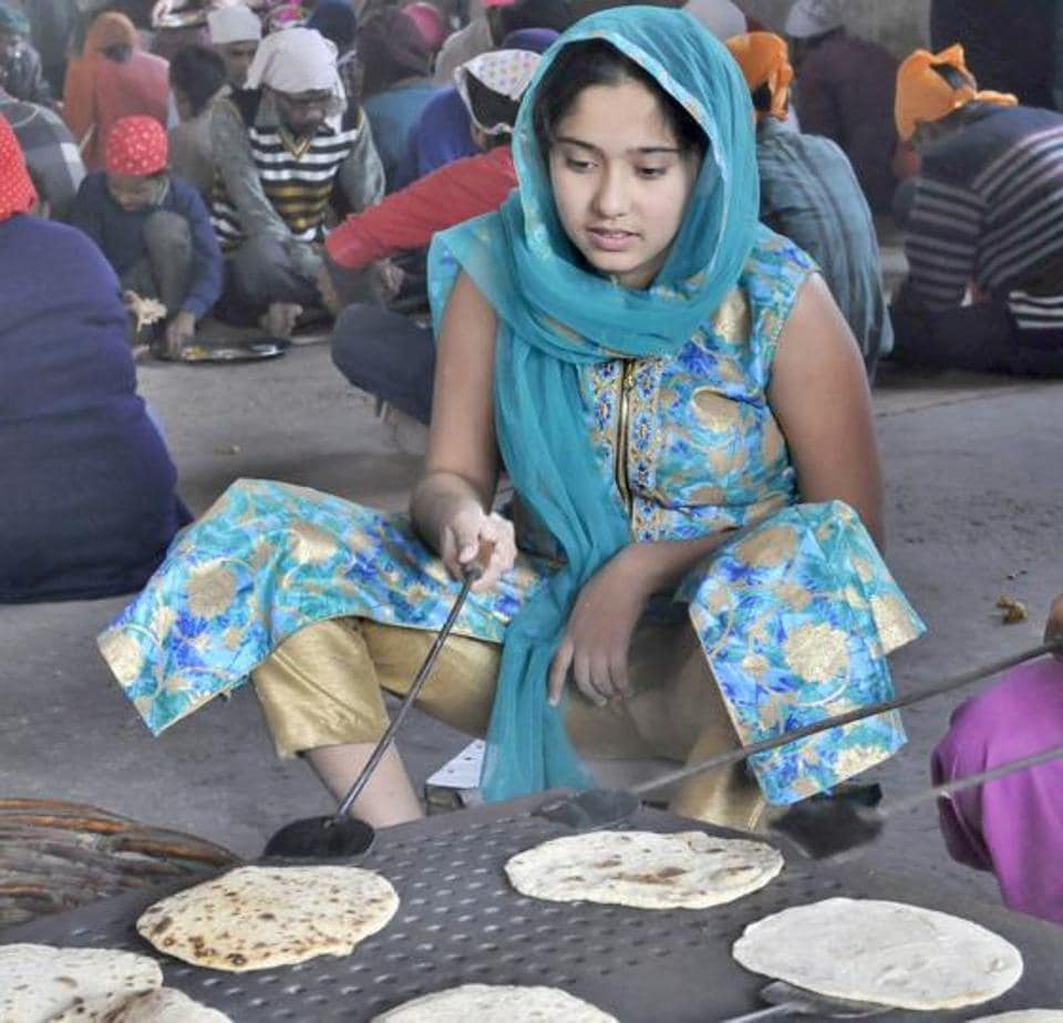 A girl helps in the community kitchen by preparing chapatis on the occasion of birth anniversary of tenth Guru of Sikhs, Guru Gobind Singh at a gurudwara in Ludhiana on Monday.  (Gurminder Singh/HT)