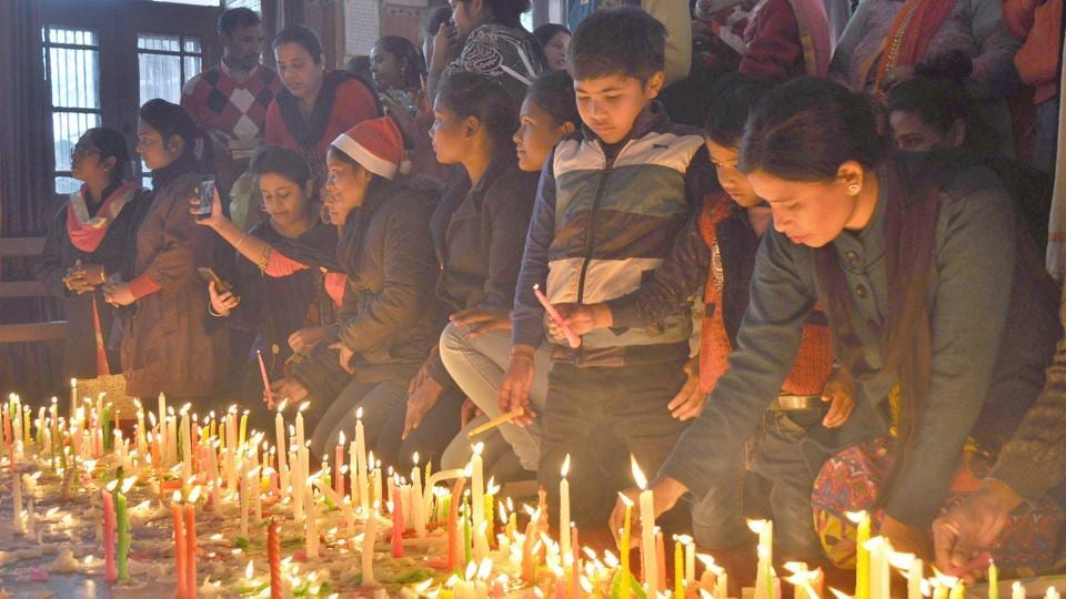 People lighting candles on the occasion of Christmas at a Church in Ludhiana on Monday. (Gurminder Singh/HT)