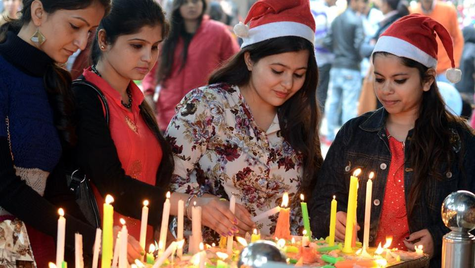 Women light candles as they celebrate Christmas at the Sacred Heart Catholic Church in Jalandhar. (Pardeep Pandit/HT )