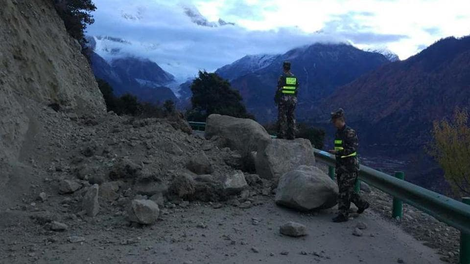 In this photo released by China's Xinhua news agency, rescuers look at a road blocked by fallen rocks in Tibet region on November 18, 2017. Experts said three artificial lakes created after the quake may pose threat to Assam and Arunachal Pradesh.(AP)