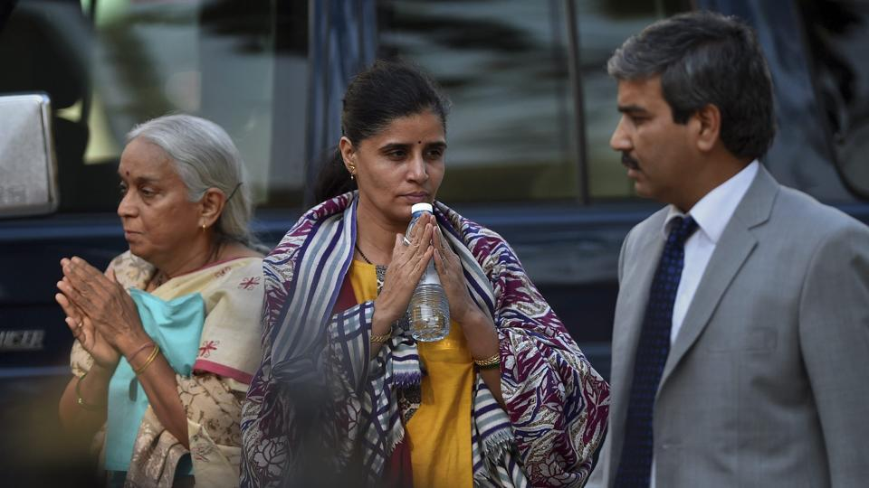 The wife centre and mother left of imprisoned Indian naval officer Kulbhushan Jadhav gesture to media upon arrival with an Indian diplomat left for meeting with Jadhav at Foreign Ministry in Islamabad on Monday
