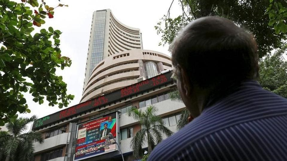 A man looks at a screen displaying the Sensex on the facade of the Bombay Stock Exchange (BSE) building in Mumbai.