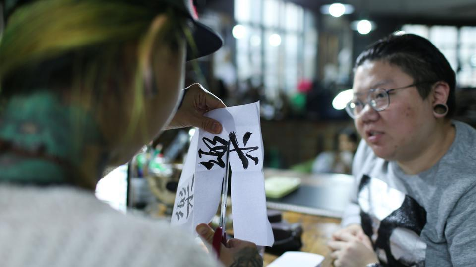 Tattoo artist Zhuo Danting, who sports a green tattoo covering the back of her neck, discusses designs with a client. Considered among China's top tattoo artists, Zhuo is among the new generation of professionals, and women, who have embraced body art.
