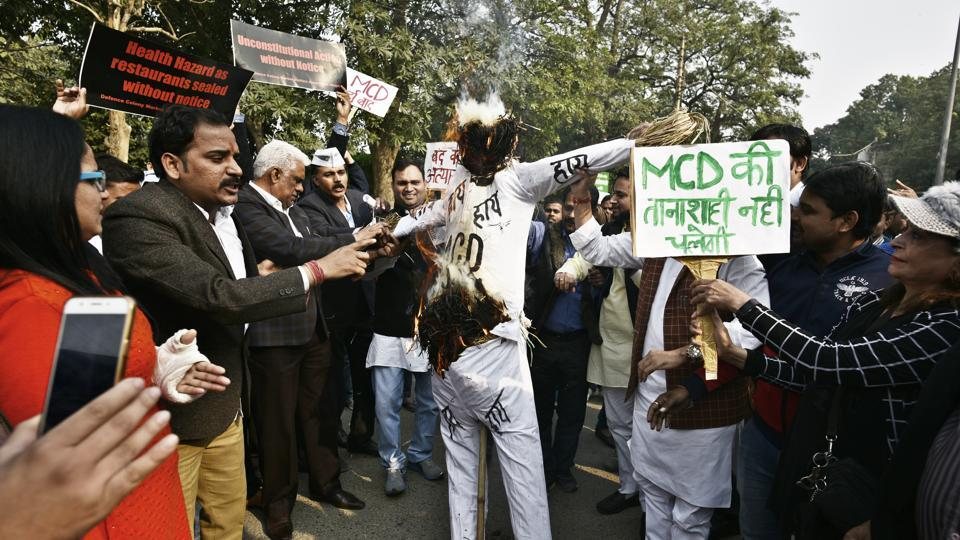 Members of the Market Association along with AAP leaders and supporters during a protest against the sealing drive at Defence Colony Market in New Delhi on Sunday.