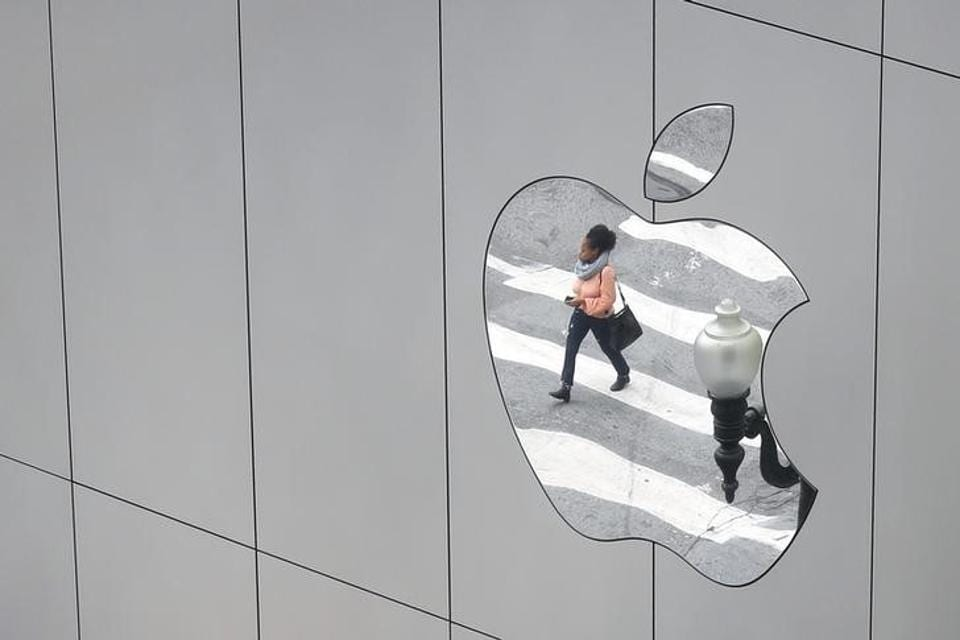 A woman is reflected in a Apple store logo in San Francisco, California, U.S., August 21, 2017. REUTERS/Kevin Coombs/Files