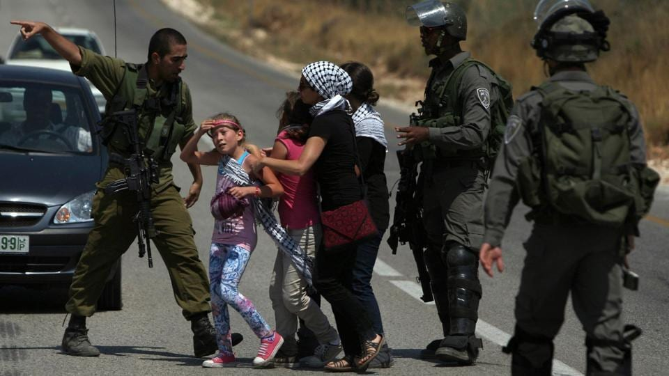 "This June 29, 2012 photo shows Israeli forces preventing Ahed Tamimi (C-L) and relatives in Nabi Saleh from going into their property which had been confiscated to expand the Halamish settlement. ""We should exact a price at some other opportunity, in the dark, without witnesses and cameras,"" columnist Ben Caspit wrote to severe criticism. ""The Tamimi family has to learn, the hard way, that such systematic provocations"" come at great cost. (Abbas Momani / AFP File)"