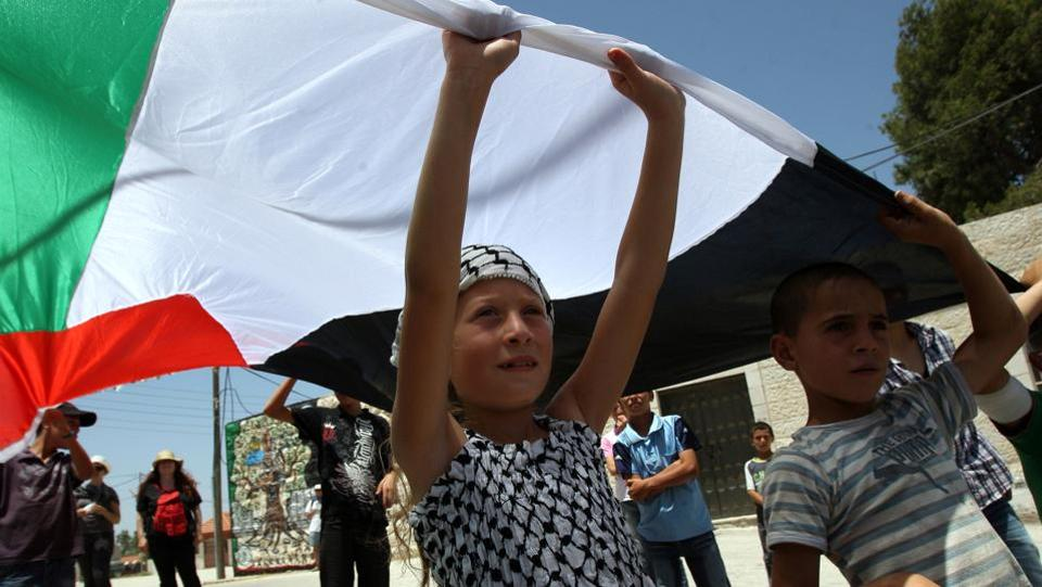 Ahed Tamimi hold up the Palestinian flag in a protest against the expropriation of Palestinian land, in Nabi Saleh on June 10, 2011. Ahed's arrest has also turned attention to Nabi Saleh's long-running disputes with the nearby Israeli settlement of Halamish, that residents say has stolen their land and water. (Abbas Momani / AFP File)