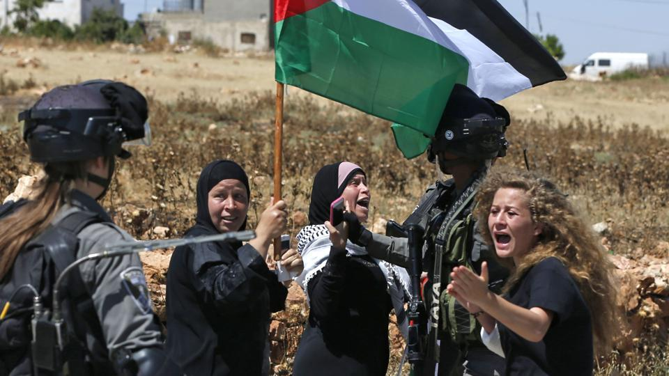 Ahed Tamimi (R) reacting in front of Israeli forces during a demonstration on May 26, 2017. The latest video, filmed in her backyard, occurred hours after a cousin was shot in the face with a rubber bullet, and was streamed live on Facebook on December 15. Her publicised arrest by the army in a night raid silenced some calls for punishment, but also launched a new social-media campaign: #FreeAhed. (Abbas Momani / AFP File)
