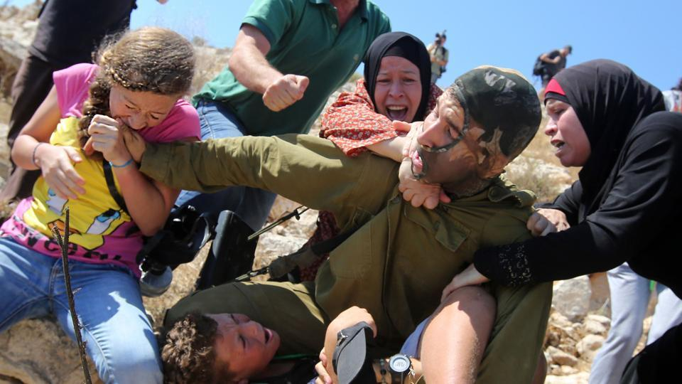 "An August 28, 2015 image shows Ahed Tamimi (L) biting the hand of an Israeli soldier, trying to free her brother during clashes in Nabi Saleh. The encounter which was also caught on video is among Ahed Tamimi's several with Israeli forces. ""Restraint is a failed and dangerous policy,"" said Oren Hazan, an Israeli member of parliament from the Likud Party. ""Next time it must end differently."" (Abbas Momani / AFP File)"