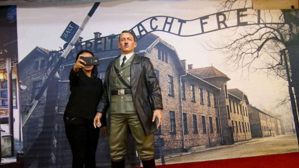 This photograph taken on November 10, 2017 shows an Indonesian woman take a selfie with a life-size wax sculpture of Adolf Hitler at a museum in Yogyakarta.