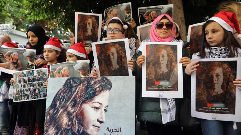 Demonstrators call for the release of Ahed Tamimi outside the International Committee of the Red Cross in Beirut on December 26, 2017. Wearing a keffiyeh over her denim jacket, Tamimi was filmed screaming in Arabic, repeatedly punching, slapping and kicking armed Israeli army officers who stood passively. As the soldiers walked away, debates spurred in Israel over whether the soldiers' restraint was virtuous or a national embarrassment. (Anwar Amro / AFP)
