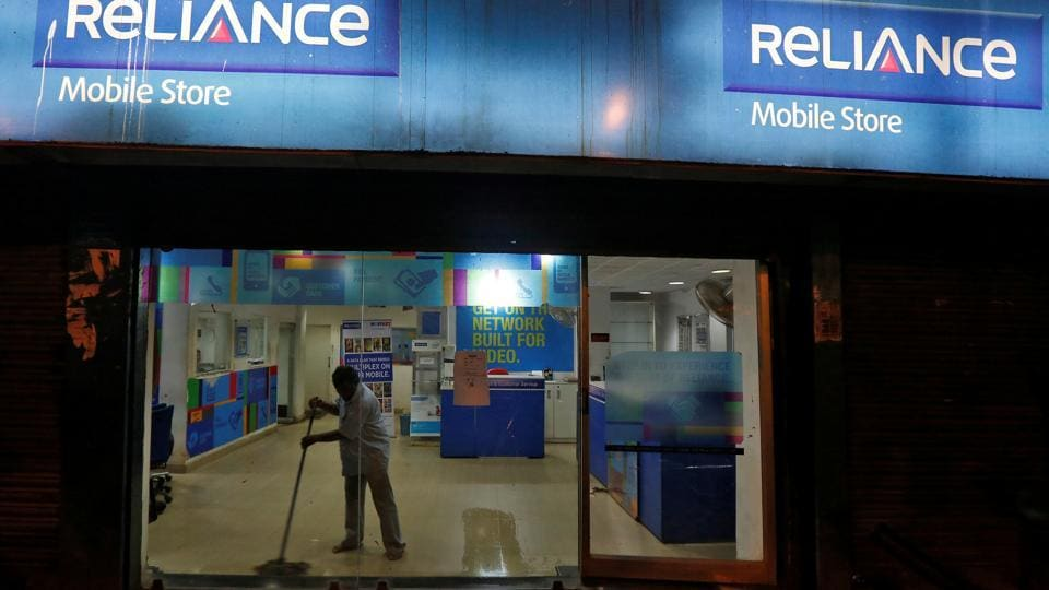 A worker cleans a mobile store of Reliance Communications Ltd in Kolkata, in September 2016.  RCom and other telecom companies have been hurt by intense price competition, and piled on debt in their quest for expansion of market share.