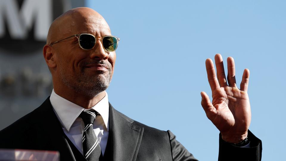 Actor Dwayne Johnson waves before unveiling his star on the Hollywood Walk of Fame in Los Angeles.