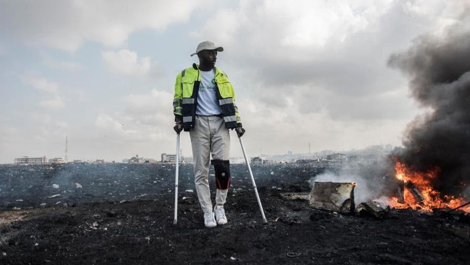 "Ghanaian artist Joseph Awuah-Darko poses for a portrait at Agbogbloshie electronic waste dumpsite in Accra, Ghana. In January 2017, Joseph co-founded the non-profit Agbogblo.Shine Initiative, which encourages people working at the dump to turn waste into high-end furniture. ""It's survival and dystopia,"" says the 21-year-old British-born Ghanaian. The dump and scrap yard sit next to the heavily polluted Odaw River, home to an estimated 40,000 people. (Cristina Aldehuela / AFP)"