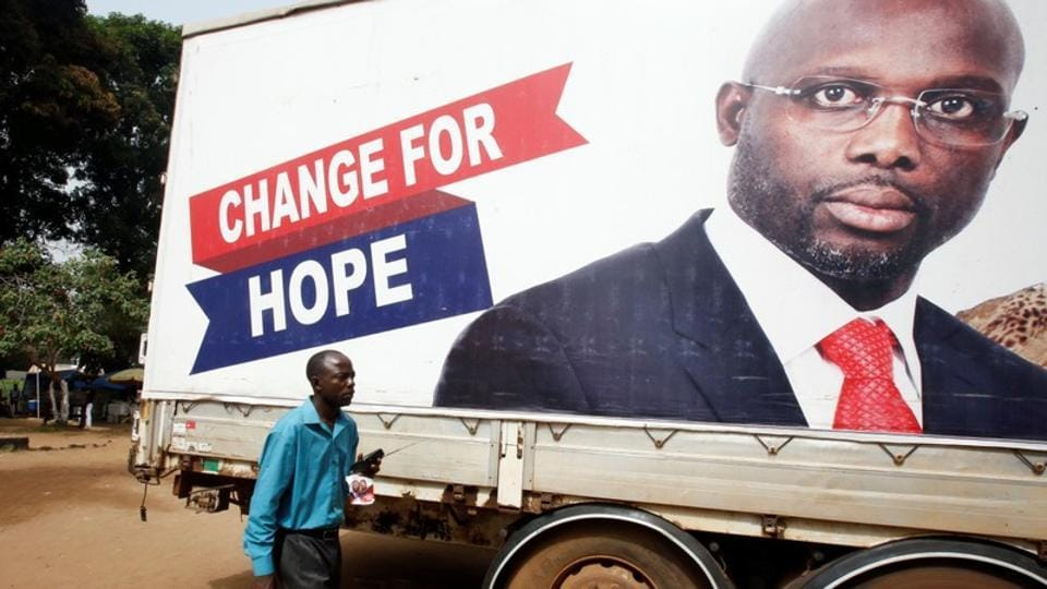 A supporter of George Weah, former football player and presidential candidate of Coalition for Democratic Change (CDC), listens to the announcement of the presidential election results on the radio, in Monrovia, Liberia on December 27. Weah is poised to win the presidential elections after two previous unsuccessful attempts.