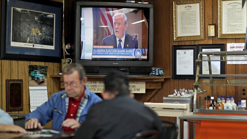 A newscast on President Trump plays as customers play cards in the Frosty Freeze restaurant in Sandy Hook, Kentucky on December 14, 2017. Everyone in town comes to this diner for nostalgia and homestyle cooking. And recently, reporters came from all over the world to puzzle over politics — because Elliott County, a blue-collar union stronghold, voted for the Democrat in each and every presidential election for its 147-year existence. Until Donald Trump came along. (David Goldman / AP)