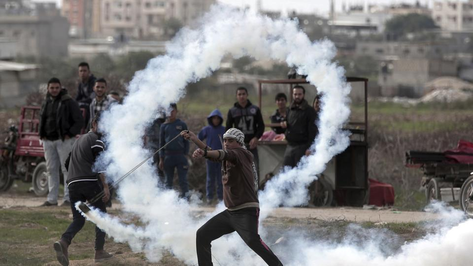 A Palestinian protester slings a tear gas canister towards Israeli soldiers during clashes on the Israeli border with Gaza on December 22, 2017. (Khalil Hamra / AP)