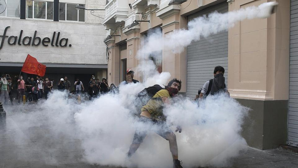 A demonstrators lobs a tear gas canister back towards the police during clashes against the pardon of former President Alberto Fujimori in Lima, Peru on December 25, 2017. Peru's President Pedro Pablo Kuczynski announced Sunday night that he granted a medical pardon to the jailed former strongman who was serving a 25-year sentence for human rights abuses, corruption and the sanctioning of death squads. (Martin Mejia / AP)