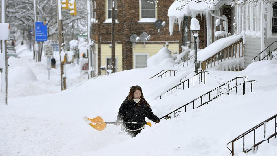 Rochelle Carlotti, 28, shovels steps near her home after a record snowfall on December 26, 2017 in Erie, Pennsylvania. The National Weather Service office in Cleveland says Monday's storm brought 34 inches of snow, an all-time daily snowfall record for Erie as a cold wave sweeps North America. (Greg Wohlford / Erie Times-News via AP)