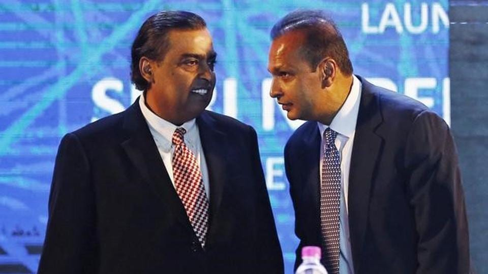 Anil Ambani (R), chairman of the Reliance Anil Dhirubhai Ambani Group, talking to his brother Mukesh Ambani, chairman of Reliance Industries Limited, in New Delhi, India, July 1, 2015.