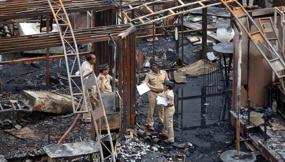 A police team inspects the debris after a fire broke out in Mumbai on Friday. At least 14 people were killed in the fire in Kamala Mills Compound in Lower Parel.