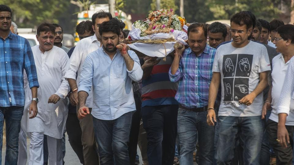 Piyush Dhirani (light blue shirt) carries his wife Kavita Dharani's body for cremation. Kavita died in a fire in Mumbai that killed 13 others on Thursday night.