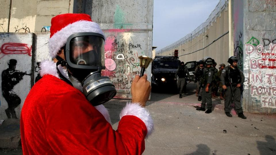 A Palestinian dressed as Santa Claus faces Israeli troops during a protest in the West Bank city of Bethlehem on December 23, 2017. (Ammar Awad / REUTERS)