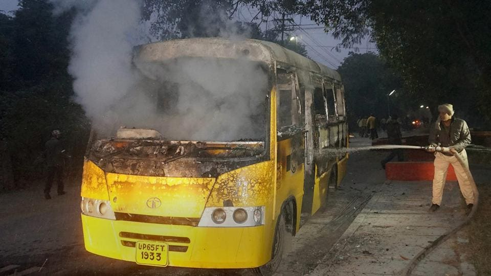 A policeman dousing the fire at a bus that was torched by a group of students who were protesting against the arrest of a student leader affiliated to the Samajwadi Party, at Banaras Hindu University in Varanasi on Wednesday.