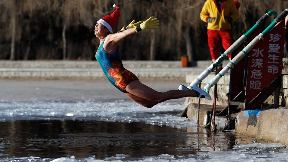 A woman wearing a Santa hat dives into a partly frozen lake in Shenyang in China's northeastern Liaoning province on December 25, 2017. (AFP)
