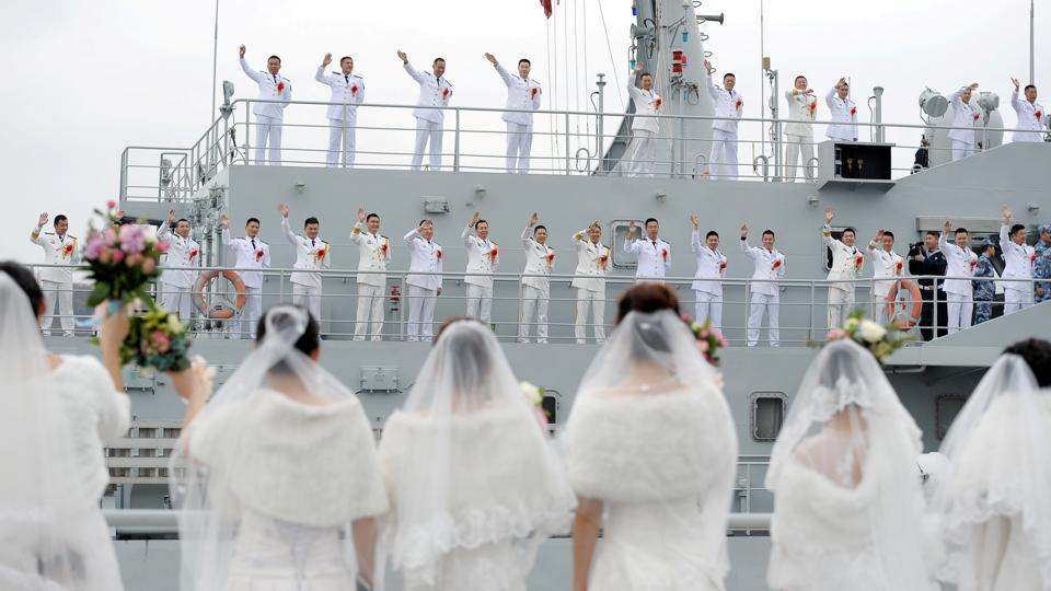 Navy personnel of the Chinese People's Liberation Army (PLA) wave at their brides during a mass wedding at a military base in Zhoushan, Zhejiang province, China on December 29, 2017. (REUTERS)