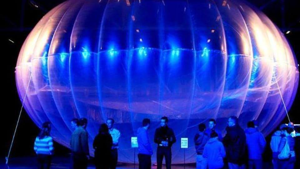 Visitors stand next to a high altitude WiFi internet hub, a Google Project Loon balloon, on display at the Airforce Museum in Christchurch.