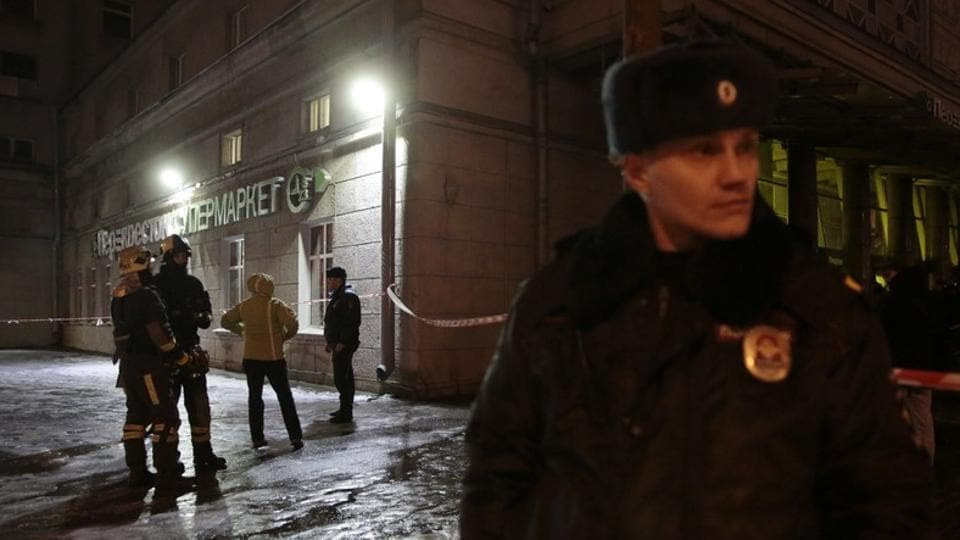Emergency Ministry members and policemen are seen outside a supermarket after an explosion in St Petersburg, Russia.