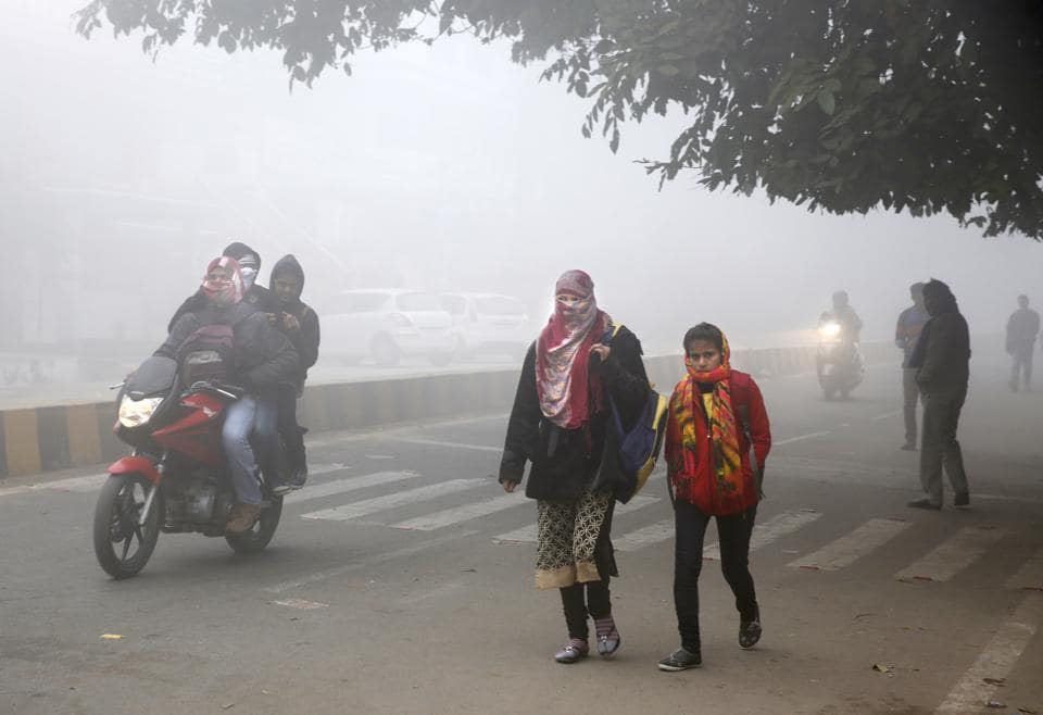 People cover themselves up with heavy woollens as they ride and walk on a cold and foggy morning in Allahabad.