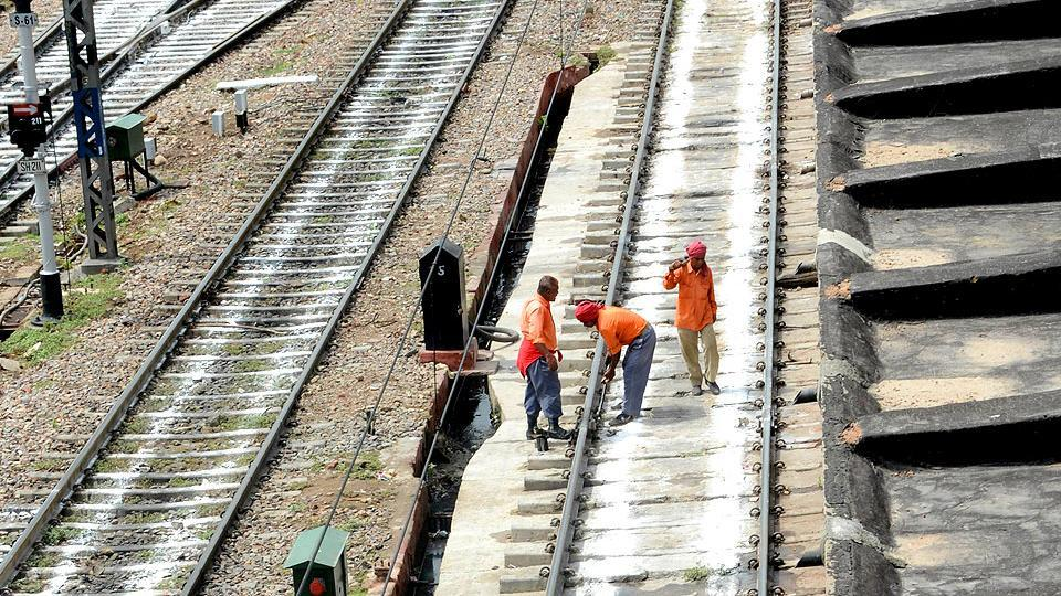Indian railway workers check the railway tracks.