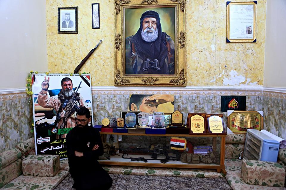 In this December 5, 2017 photo, a man sits among awards, certificates of appreciation and posters belonging to the sniper Ali Jayad al-Salhi, 65, a volunteer with Popular Mobilization Forces killed fighting Islamic State militants, in Basra, 340 miles (550 kilometers) southeast of Baghdad, Iraq.