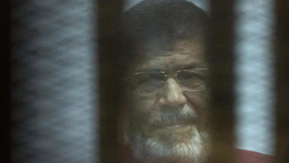In this April 23, 2016, file photo, ousted Egyptian President Mohammed Morsi, wearing a red jumpsuit that designates he has been sentenced to death, sits inside a defendants cage in a makeshift courtroom at the national police academy, in an eastern suburb of Cairo, Egypt.