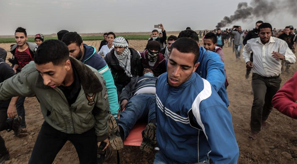 Palestinian protesters carry a wounded comrade during clash with Israeli forces near the Israel-Gaza border east of the southern Gaza strip city of Khan Yunis on December 29, 2017.