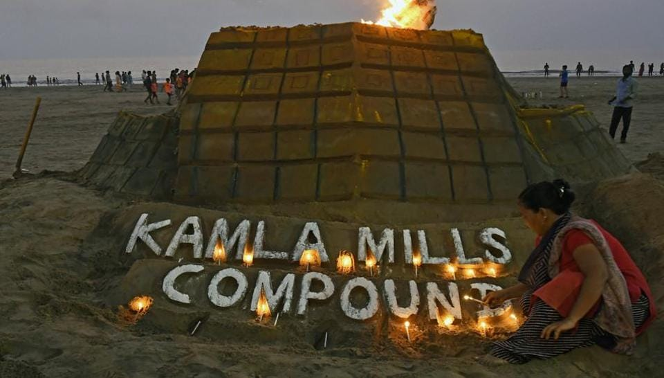 Sand artists light a candle on a structure created to commemorate  victims of the Kamala Mills tragedy at Juhu Beach in Mumbai on Saturday.