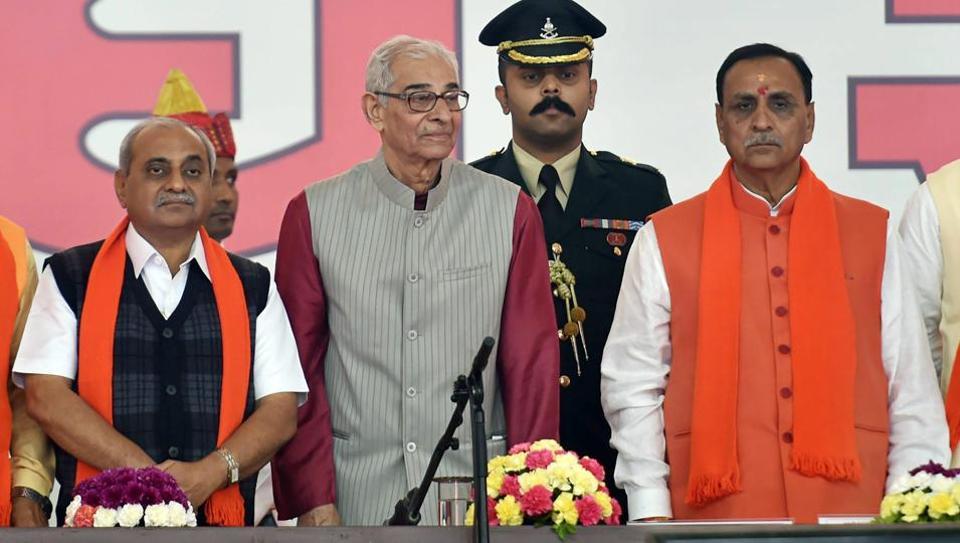 Gujarat CM Vijay Rupani (right) and deputy CM Nitin Patel (left) along with governor Om Prakash Kohli during the swearing-in ceremony at Gandhinagar.