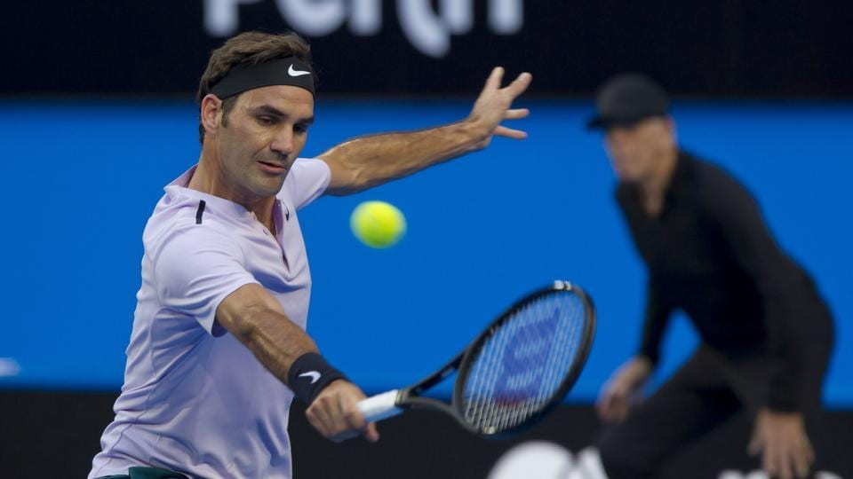 Roger Federer of Switzerland hits a return against Yuichi Sugita of Japan during their second session men's singles match on day one of the Hopman Cup tennis tournament in Perth on December 30, 2017.