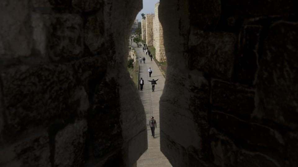 People coursing through Jerusalem's Old City seen trough the city walls at Jaffa Gate. Today, the 2.5-mile (4 kilometer) circuit around the Old City brings visitors face-to-face with Jews, Muslim and Christian Arabs, Armenians, men and women of the cloth and tourists from around the globe. (Oded Balilty / AP)