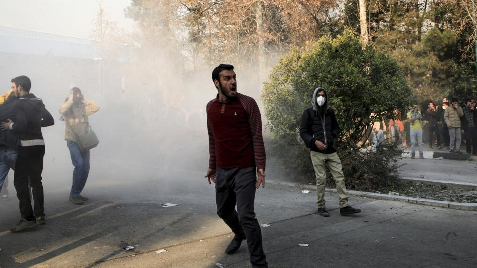 University students attend a protest inside Tehran University while a smoke grenade is thrown by anti-riot Iranian police, in Tehran.