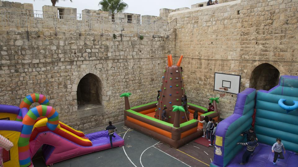 Israeli Arab Christian school kids play in De La Salle School's basketball yard surrounded by the Old City walls next to the New Gate. Amid prolonged political conflicts spanning decades, day-to-day life continues to flourish within these historic sand-hued stone walls. (Oded Balilty / AP)