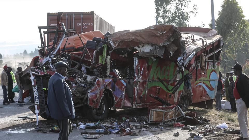 People look at the wreckage of a bus and a lorry that crashed in a head-on collision at the accident scene near Nakuru, Kenya, on December 31, 2017.