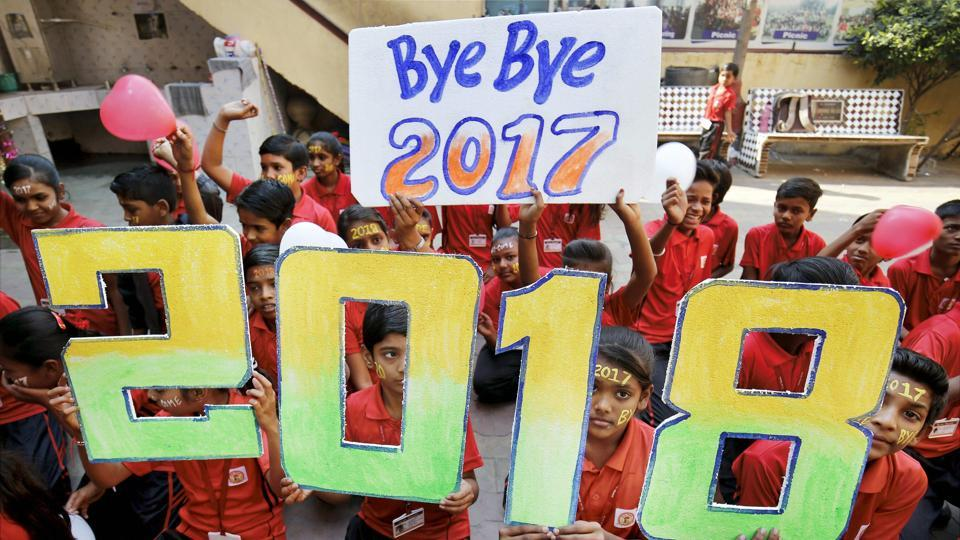 Students pose with placards that read '2018', to give out new year wishes, in Ahmedabad on Saturday.
