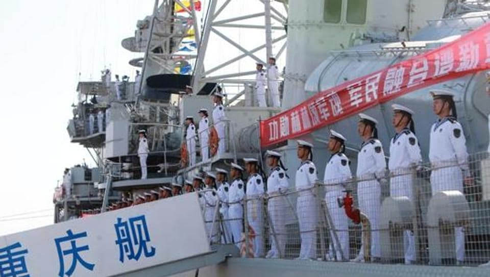 Chinese People's Liberation Army navy soldiers stand on a decommissioned destroyer in an aircraft carrier theme park during a celebration event on China's Navy Day at Binhai New Area, Tianjin, China, April 23, 2017.