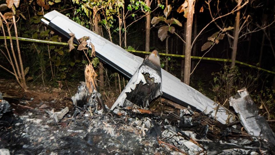 The tail of the burned fuselage of a small plane that crashed, rests near trees in Guanacaste, Costa Rica on Sunday.