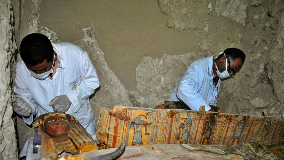 Members of an Egyptian archaeological team work on a wooden coffin discovered in a 3,500-year-old tomb in the Draa Abul Nagaa necropolis, near the southern Egyptian city of Luxor, on April 18, 2017.